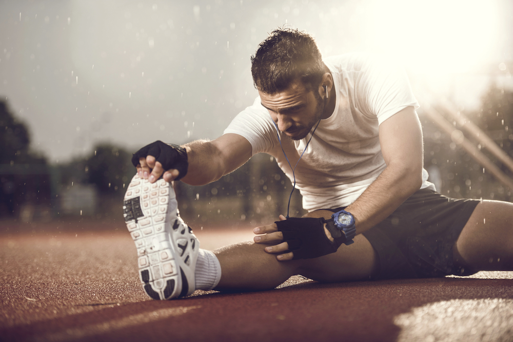 Young athlete doing stretching exercises on a rain.